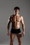 Ισχυρό αθλητικό άτομο που παρουσιάζει το μυϊκά σώμα και sixpack ABS Showi Στοκ Φωτογραφία