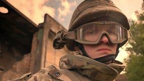 Ισχυρό καυκάσιο άτομο που φορά τη στρατιωτική στολή στην κάλυψη και το κράνος που εξετάζει κατ' ευθείαν και έπειτα τη κάμερα, επί απόθεμα βίντεο