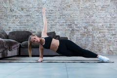 Ισχυρό καυκάσιο κορίτσι που κάνει τη δευτερεύουσα άσκηση σανίδων που ασκεί Pilates στο σπίτι στοκ εικόνες
