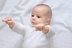 Ισχυρό υγιές μωρό που εξετάζει τις πυγμές στοκ εικόνα