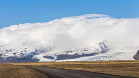 Ισλανδική περιφερειακή οδός που περνά από Vatna Glacier Vatnajökull με τα σύννεφα πέρα από τα βουνά Στοκ Φωτογραφίες