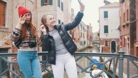 Ιταλία, Βενετία Δύο νέοι ταξιδιώτες γυναικών που στέκονται στη μικρή γέφυρα και που παίρνουν selfies σε ένα υπόβαθρο ενός νερού απόθεμα βίντεο