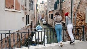 Ιταλία, Βενετία Δύο νέοι ταξιδιώτες γυναικών που στέκονται στη μικρή γέφυρα πέρα από το νερό διοχετεύουν και που απολαμβάνουν τη  απόθεμα βίντεο