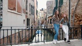 Ιταλία, Βενετία Δύο νέοι ταξιδιώτες γυναικών που στέκονται στη μικρή γέφυρα πέρα από το νερό διοχετεύουν και που μιλούν ο ένας στ απόθεμα βίντεο