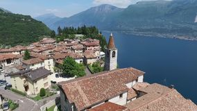 Ιταλία Εκκλησία στο βουνό και την παλαιά πόλη Πανόραμα της πανέμορφης λίμνης Garda που περιβάλλεται από τα βουνά βίντεο απόθεμα βίντεο