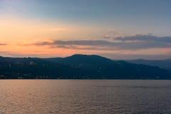 Ιταλία, Arona, που εξισώνει την άποψη της πόλης από τη λίμνη Σκιαγραφία της πόλης στο ηλιοβασίλεμα Στοκ φωτογραφία με δικαίωμα ελεύθερης χρήσης