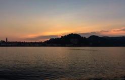 Ιταλία, Arona, που εξισώνει την άποψη της πόλης από τη λίμνη Σκιαγραφία της πόλης στο ηλιοβασίλεμα Στοκ Φωτογραφίες