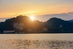 Ιταλία, Arona, που εξισώνει την άποψη της πόλης από τη λίμνη Σκιαγραφία της πόλης στο ηλιοβασίλεμα Στοκ Εικόνα