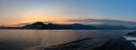 Ιταλία, Arona, που εξισώνει την άποψη της πόλης από τη λίμνη Σκιαγραφία της πόλης στο ηλιοβασίλεμα Στοκ Εικόνες