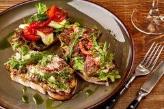 Ιταλικά σάντουιτς - bruschetta με το πατέ κρέατος, το arugula, την ξηραμένους από τον ήλιο ντομάτα και τους σπόρους στο ψωμί στο  Στοκ Φωτογραφία