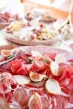 Ιταλικά antipasti και ορεκτικά πίνακας με το prosciutto φετών, σαλάμι, ξηρό χοιρινό κρέας, ζαμπόν σαλαμιού με τα χορτάρια Στοκ εικόνα με δικαίωμα ελεύθερης χρήσης