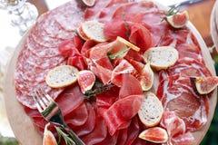 Ιταλικά antipasti και ορεκτικά πίνακας με το prosciutto φετών, σαλάμι, ξηρό χοιρινό κρέας, ζαμπόν σαλαμιού με τα χορτάρια Στοκ Εικόνα