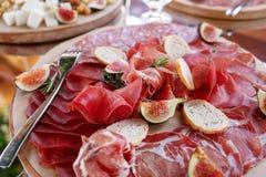 Ιταλικά antipasti και ορεκτικά πίνακας με το prosciutto φετών, σαλάμι, ξηρό χοιρινό κρέας, ζαμπόν σαλαμιού με τα χορτάρια Στοκ Εικόνες
