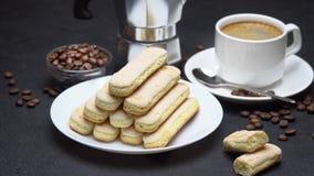 Ιταλικά ladyfingers Savoiardi μπισκότα και φλιτζάνι του καφέ στο συγκεκριμένο υπόβαθρο φιλμ μικρού μήκους