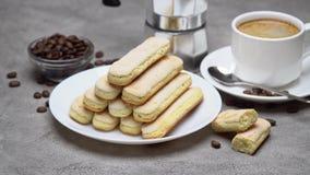 Ιταλικά ladyfingers Savoiardi μπισκότα και φλιτζάνι του καφέ στο συγκεκριμένο υπόβαθρο απόθεμα βίντεο