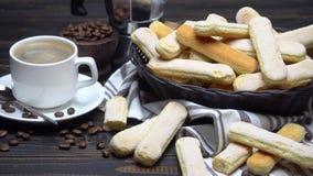 Ιταλικά ladyfingers Savoiardi μπισκότα στο καλάθι και τον καφέ στο ξύλινο υπόβαθρο απόθεμα βίντεο
