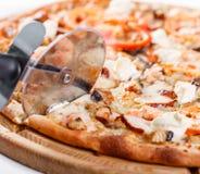 Ιταλική έννοια κουζινών και μαγειρέματος - μαγειρεψτε με τον κόπτη την τέμνουσα πίτσα στα κομμάτια στο pizzeria Νόστιμος που τεμα στοκ εικόνες