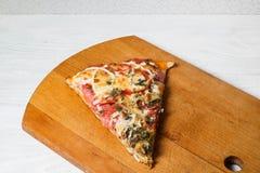 Ιταλική αγροτική πίτσα, ένα κομμάτι σε έναν ξύλινο δίσκο, άσπρος ξύλινος πίνακας στοκ εικόνα