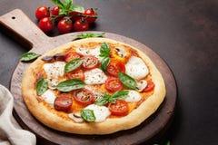 Ιταλική πίτσα με τις ντομάτες, τη μοτσαρέλα και το βασιλικό στοκ φωτογραφία