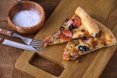 Ιταλική πίτσα φετών με pepperoni το λουκάνικο, ζαμπόν, ελιά, βασιλικός Στοκ Εικόνες