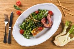 Ιταλική σαλάτα με το χταπόδι Σαλάτα με τις ντομάτες θαλασσινών, arugula και κερασιών Πικάντικη σαλάτα σε ένα άσπρο πιάτο σε έναν  Στοκ φωτογραφία με δικαίωμα ελεύθερης χρήσης