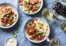 Ιταλικός πίνακας τροφίμων Ζυμαρικά με το αργό κοτόπουλο κουζινών με τις ελιές και τα γλυκά πιπέρια, άσπρο κρασί Ένα ξηρό πρόγευμα Στοκ Εικόνες