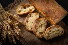 Ιταλικό παραδοσιακό ψωμί ciabatta με τα τεμαχισμένα κομμάτια †‹â€ ‹και τα αυτιά του σίτου σε μια πετσέτα γιούτας σε έναν πίνακα στοκ φωτογραφίες