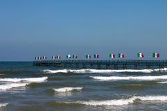 Ιταλία Αιμιλία-Ρωμανία Rimini Ομάδα σημαιών της Ιταλίας και της θάλασσας στο υπόβαθρο μπλε ουρανού καλλιτεχνικά λεπτομερή οριζόντ Στοκ εικόνα με δικαίωμα ελεύθερης χρήσης
