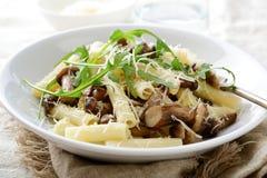 Ιταλικά παραδοσιακά ζυμαρικά με τα μανιτάρια και arugula στο λευκό Στοκ εικόνες με δικαίωμα ελεύθερης χρήσης