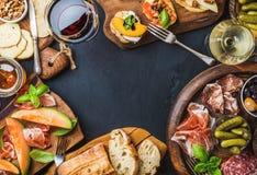Ιταλικά πρόχειρα φαγητά κρασιού antipasti που τίθενται πέρα από το μαύρο υπόβαθρο grunge Στοκ εικόνα με δικαίωμα ελεύθερης χρήσης