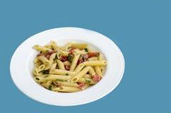 Ιταλικά τρόφιμα: Αποκαλούμενο ζυμαρικά mezze pennette με τις ντομάτες στα κομμάτια Στοκ Εικόνες