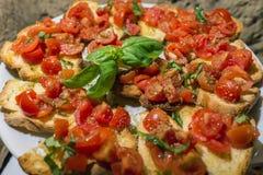 Ιταλικά bruschettas με την τεμαχισμένους ντομάτα και το βασιλικό έτοιμους για το brea Στοκ Φωτογραφίες