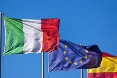 Ιταλικές ευρωπαϊκές και ισπανικές σημαίες στο μπλε ουρανό Στοκ Φωτογραφία