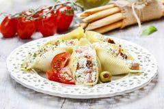 Ιταλική κουζίνα: γεμισμένοι κοχύλια ζυμαρικών και σωρός των breadsticks. Στοκ φωτογραφία με δικαίωμα ελεύθερης χρήσης