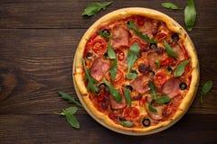 Ιταλική πίτσα με το ζαμπόν, τις ντομάτες, τις ελιές, το τυρί και το διεσπαρμένο arugula στο αγροτικό ξύλινο υπόβαθρο Στοκ φωτογραφίες με δικαίωμα ελεύθερης χρήσης