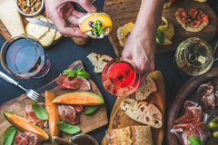 Ιταλική ποικιλία πρόχειρων φαγητών κρασιού, man& x27 τα χέρια του s που κρατούν το γυαλί αυξήθηκαν Στοκ Εικόνες