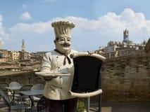 Ιταλικός αρχιμάγειρας με την πανοραμική άποψη της Σιένα σχετικά με δικούς του  Στοκ φωτογραφία με δικαίωμα ελεύθερης χρήσης