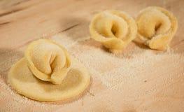 Ιταλικό σπιτικό tortellini που τοποθετείται στον ξύλινο πίνακα που ψεκάζεται με το αλεύρι Στοκ φωτογραφία με δικαίωμα ελεύθερης χρήσης