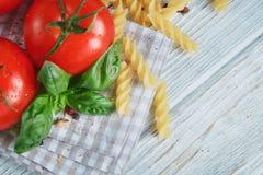 Ιταλικό υπόβαθρο τροφίμων με τις ντομάτες, βασιλικός, ζυμαρικά, ελαιόλαδο, Στοκ Φωτογραφίες