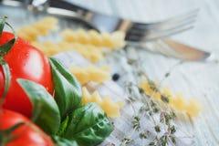 Ιταλικό υπόβαθρο τροφίμων με τις ντομάτες, βασιλικός, ζυμαρικά, ελαιόλαδο, Στοκ φωτογραφία με δικαίωμα ελεύθερης χρήσης