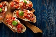Ιταλικό bruschetta με τις ψημένες ντομάτες, τυρί μοτσαρελών και Στοκ Φωτογραφίες