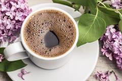 Ιώδεις λουλούδια και καφές στο άσπρο φλυτζάνι Στοκ Φωτογραφίες