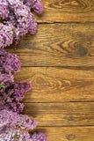 Ιώδη λουλούδια σε ένα ξύλινο υπόβαθρο, πλαίσιο Στοκ Εικόνες