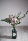 Ιώδες λουλούδι σε ένα πράσινο βάζο στο ξύλινο υπόβαθρο Στοκ εικόνα με δικαίωμα ελεύθερης χρήσης