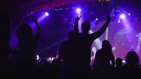 Ιώδες φως στη σκηνή - πολλοί άνθρωποι που χορεύουν στη συναυλία Στοκ Εικόνα