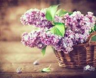 Ιώδης δέσμη λουλουδιών σε ένα καλάθι πέρα από το θολωμένο ξύλινο υπόβαθρο στοκ φωτογραφία με δικαίωμα ελεύθερης χρήσης