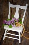 Ιώδης ανθοδέσμη με την καρδιά σχοινιών στην καρέκλα Στοκ Εικόνες