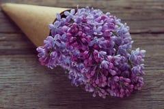 Ιώδης ανθοδέσμη λουλουδιών σε μια κορνέτα εγγράφου τεχνών παλαιό στον ξύλινο Στοκ φωτογραφίες με δικαίωμα ελεύθερης χρήσης