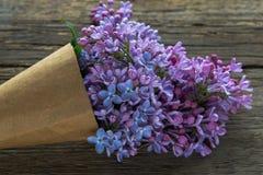Ιώδης ανθοδέσμη λουλουδιών σε μια κορνέτα εγγράφου τεχνών παλαιό στον ξύλινο Στοκ Εικόνες