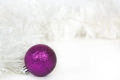 Ιώδης σφαίρα και άσπρο tinsel Χριστουγέννων Στοκ Εικόνες